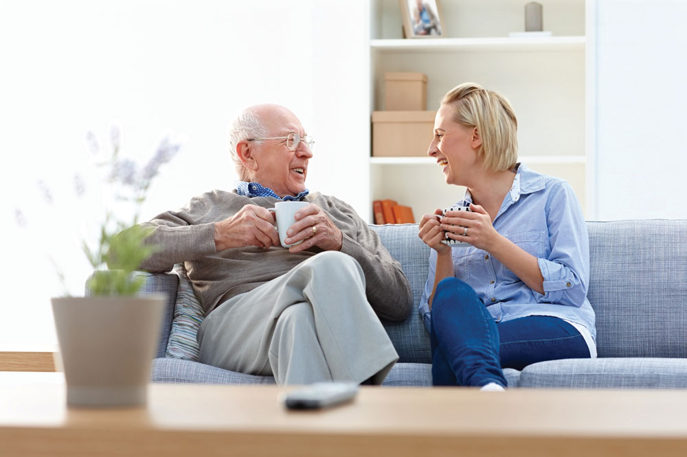 Park Louisville - Memory Care - Older male flourish memory care program resident and young female sit on couch and hold coffee mugs