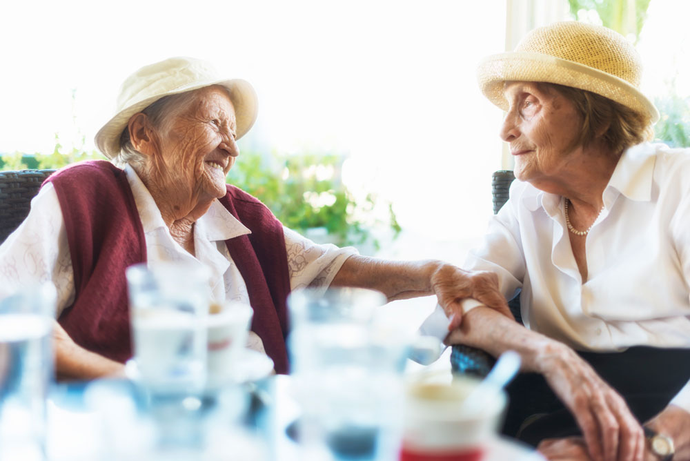 Park Louisville - Memory Care - Two female Park Louisville residents wearing hats smile at each other and sit at an outdoor table